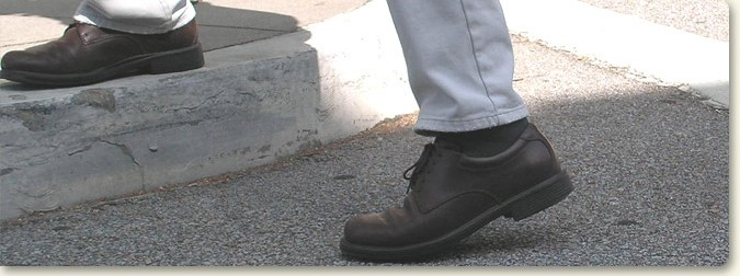 a pedestrian stepping on to the curb