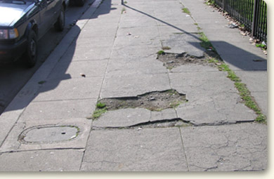 Two large potholes in sidewalk and utility cover